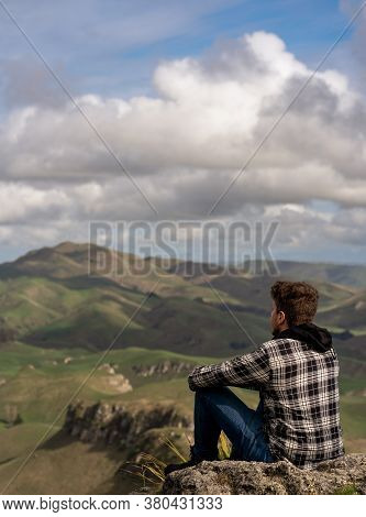 Caucasian Man Sitting At The Top Of The Mountain And Contemplating The Landscape. Vertical Photograp