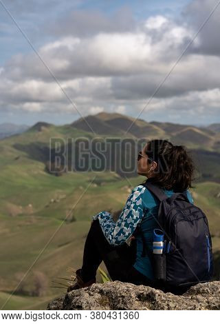 Woman Sitting And Contemplating The Scenery At The Peak Of A Mountain