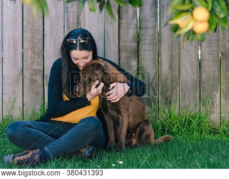 Brunette Woman Sitting On The Grass Cuddling Her Dog In The Garden, A Labrador Shar Pei Mix. Horizon
