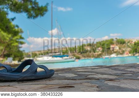 Closeup View A Rubber Slipper On The Shore Of The Sea, Blurred Sailboats, Hills And Teal Sea In The