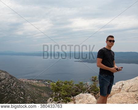 Young Adult Man Posing On Top Of The Vidova Gora Mountain, Highest Point Of The Island Brac. Popular