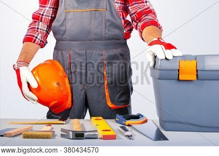 Builder Handyman With Construction Tools Against Grey Wall.