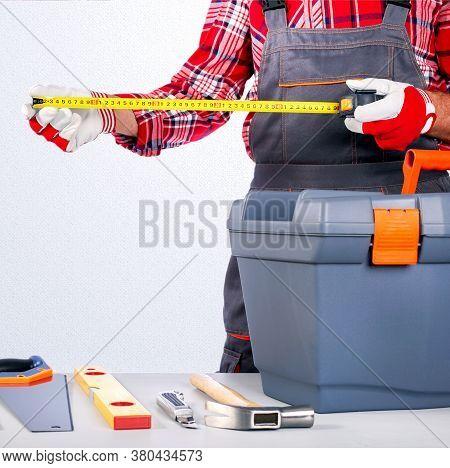 Repairman Working With Measurement Tape. Repair Home Concept.