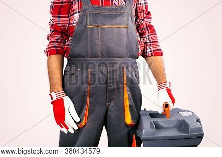 Handyman Or Technician Hold A Toolbox. Builder Carrying Toolbox Against Grey Background.