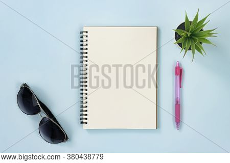Spiral Notebook Or Spring Notebook In Unlined Type And Office Plant And Glasses And Red Pen On Blue