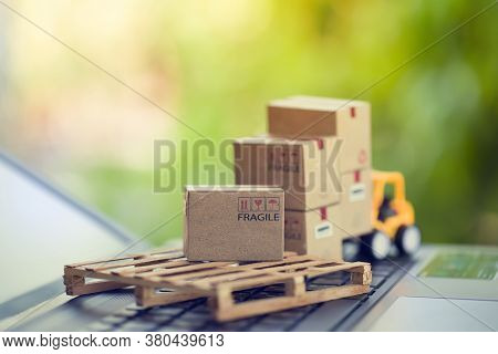 Logistic And Cargo Freight Concept: Fork-lift A Truck Moves A Paper Box On Notebook Keyboard In The