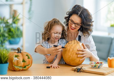 Happy family preparing for Halloween. Mother and child carving pumpkins at home.