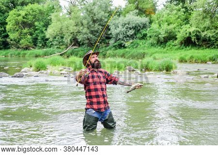 Fisher Masculine Hobby. Fisher Fishing Equipment. Fish On Hook. Brutal Man Wear Rubber Boots Stand I