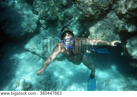 Scuba Diver Coral With Mask Snorkel And Flippers Rises To The Surface Against The Background Of Blue