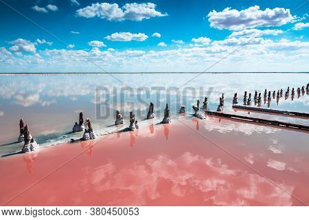 Pink Salt Lake And Sky With White Clouds Reflected In The Water Sueface. Salt Industry On Sasyk-siva