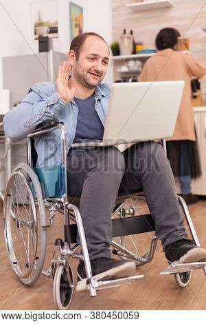 Disabled Entrepreneur In Wheelchair Waving During A Video Call On Laptop While Wife Is Cooking Lunch
