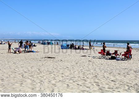 August 3, 2020 In Pismo Beach, Ca:  People Sunbathing On The Sandy Beach And Swimming In The Ocean T