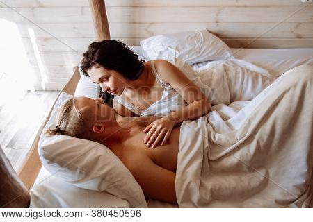 A Young Man And Woman Are Basking In Bed Together. They Are Lying Under White Sheets. A Young Man An