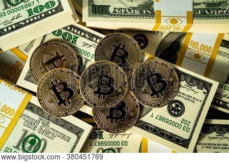 Bitcoin cryptocurrency and US dollars cash - photo of golden bitcoins physical gold coins on us dollars. Making money with bitcoin.