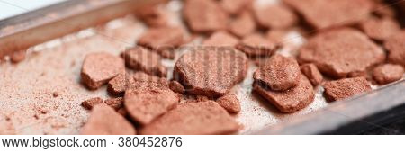 Close-up Of Construction Site Waste Laying In Metal Container. Macro Shot Of Used Clay Materials For