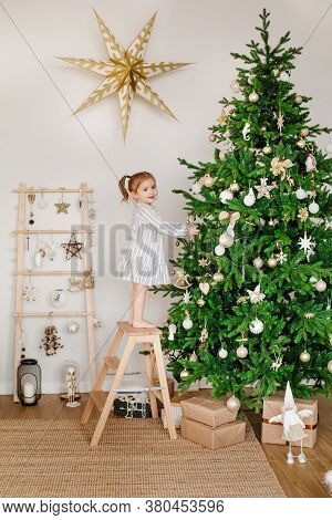 A Three-year-old Girl Is Decorating A Christmas Tree. Children, Family And Holiday Concept. Christma