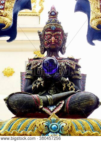 Chiang Rai. Thailand, June 16, 2017: Wat Rong Suea Ten. Blue Sculpture With A Crystal Ball In Hands