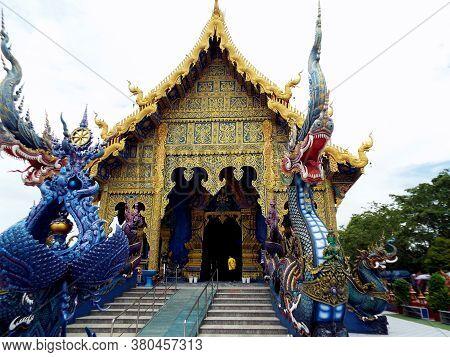 Chiang Rai. Thailand, June 16, 2017: Wat Rong Suea Ten. Main Facade With Surreal Dragons Of The Blue
