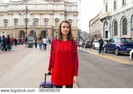 Young woman walking with her trolley in a city street