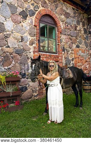 Pretty Woman With Curly Hair Standing Next To A Horse At The Stable In Valmiera, Latvia