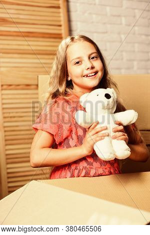 Happy Childhood. Small Child Prepare Toys For Relocation. Kid Girl Relocating Boxes Background. Relo
