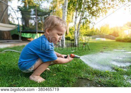 Cute Adorable Caucasian Blond Toddler Boy Enjoy Having Fun Watering Garden Flower And Lawn With Hose