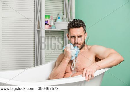 Man Wash Muscular Body With Foam Sponge. Macho Sitting Naked In Bathtub Washing With Sponge. Persona
