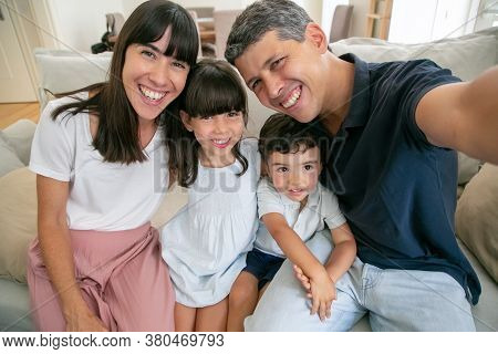 Joyful Parents And Two Kids Sitting On Couch At Home Together, Taking Selfie, Dad Holding Camera In