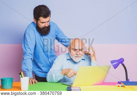 Two Different Generations Ages Sitting At Desk With Laptops. Adult Son Teaching Mature Senior Dad To