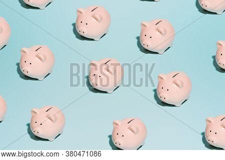 Pink piggy piggy banks on empty blue background