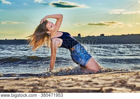 A Young Brunette Girl In A Black T-shirt And Denim Shorts Kneels On The Sandy Shore Near The Water's