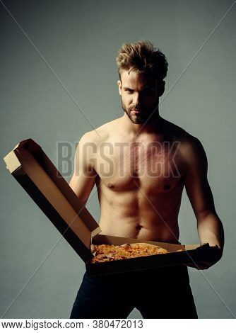 Strong Brutal Bearded Man Holding An Italian Tasty Pizza Isolated At Gray Background. Sexy Pizza Del
