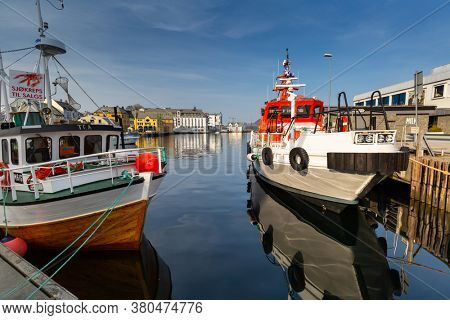 Alesund, Norway - April 14, 2018: Colorful architecture of Alesund reflected in the water of the harbour, Norway