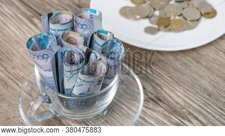 Kazakhstan Tenge In A Cup And On A Plate On The Table.a Lot Of Kazakh Money.sawing The Budget,the Su