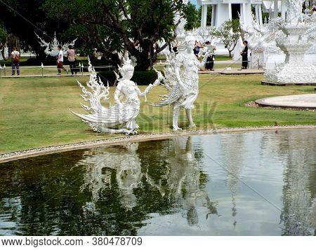 Chiang Rai. Thailand, June 17, 2017: Wat Rong Khun. Surreal Sculpture Reflected In Lake Water At The