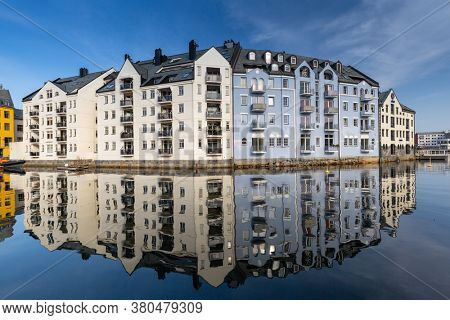 Alesund, Norway - April 14, 2018: Beautiful architecture of Alesund reflected in the water of the harbour, Norway