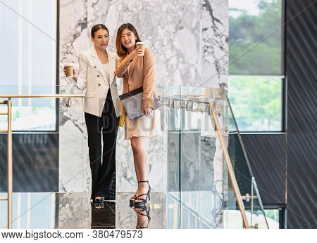 Two Asian Businesswomen Walking And Talking During Coffee Break In Modern Office Or Coworking Space,