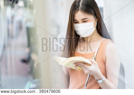 Young Asian Woman Passenger Wearing Surgical Mask And Reading The Book In Subway Train When Travelin