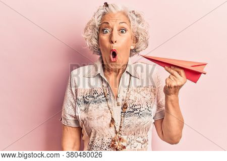 Senior grey-haired woman holding paper airplane scared and amazed with open mouth for surprise, disbelief face
