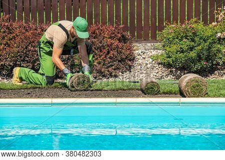 New Grass Turfs Installation Along Side Of Garden Outdoor Swimming Pool. Caucasian Gardener In His 4