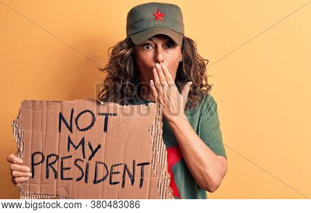 Middle age brunette communist woman holding banner with not my president message covering mouth with hand, shocked and afraid for mistake. Surprised expression