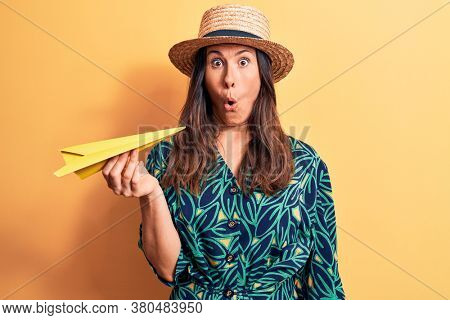 Young beautiful brunette woman wearing summer hat holding yellow paper airplane scared and amazed with open mouth for surprise, disbelief face