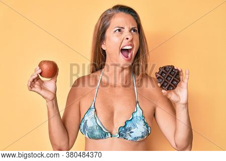 Middle age hispanic woman holding apple and donut angry and mad screaming frustrated and furious, shouting with anger. rage and aggressive concept.