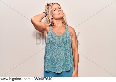 Middle age caucasian blonde woman wearing sportswear confuse and wondering about question. uncertain with doubt, thinking with hand on head. pensive concept.