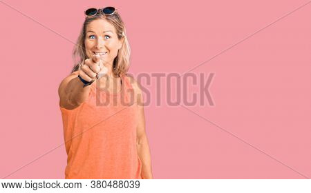 Middle age fit blonde woman wearing casual summer clothes and sunglasses pointing displeased and frustrated to the camera, angry and furious with you