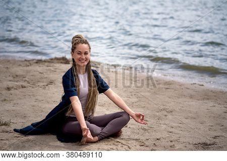 A Young Girl Smiles, Sits In The Lotus Position And Meditates On The Beach. Close-up. Online Trainin