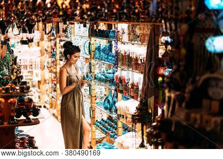 Beautiful woman in a souvenir shop in Turkey. Girl chooses a souvenir. Oriental shop. Turkish Souvenirs. Oriental bazaar. Turkish Bazaar. Gift shop in Goreme, Turkey. Moroccan Bazaar. Copy space.