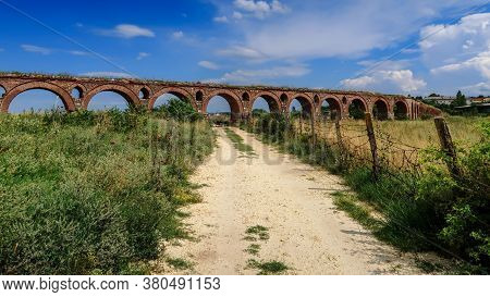 Path Leads Towards At The Ruins Of Ancient Aqueduct In The Middle Of A Field At The Outskirts Of Sko