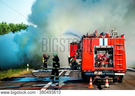 Firefighter Extinguishes A Burning Car After An Accident, Fireman Using Water And Extinguisher Car I