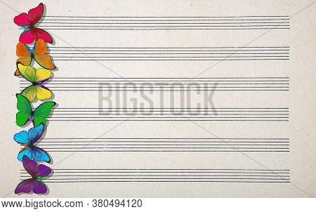 Colors Of Rainbow. Colorful Multicolored Morpho Butterflies On Music Sheet. Old Music Sheet Texture